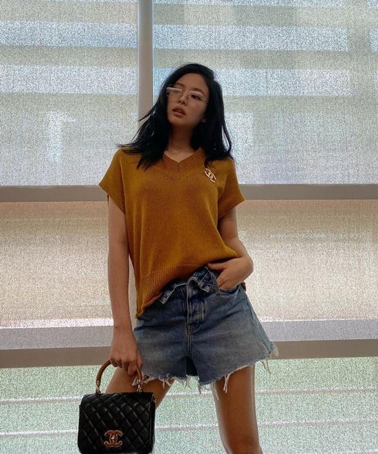 Thánh Chanel Jennie phối áo len với quần short jeans không đóng cúc, tạo dáng sang chảnh như chụp hình tạp chí.