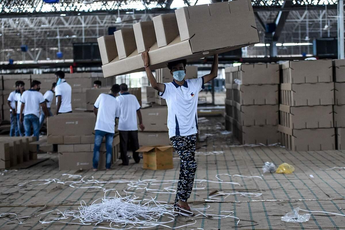 Công nhân vận chuyển giường carton để lắp ráp tại trung tâm tạm thời. Ảnh: AFP.