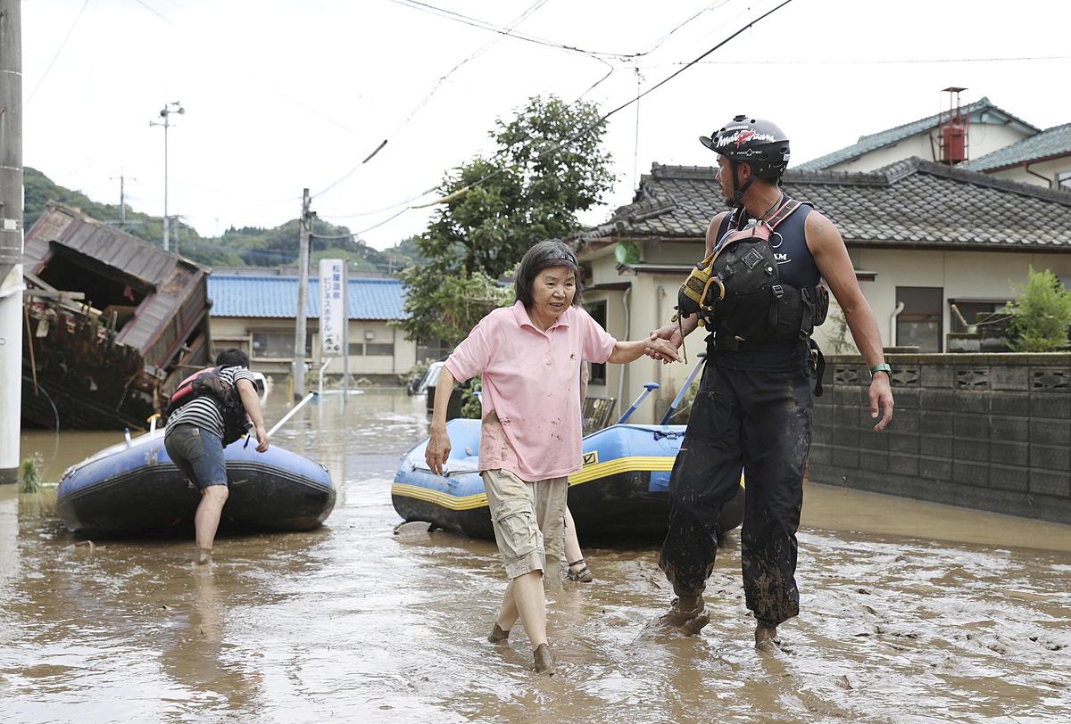 Một nhân viên cứu hộ đưa người dân đi sơ tán. Ảnh: Kyodo News.