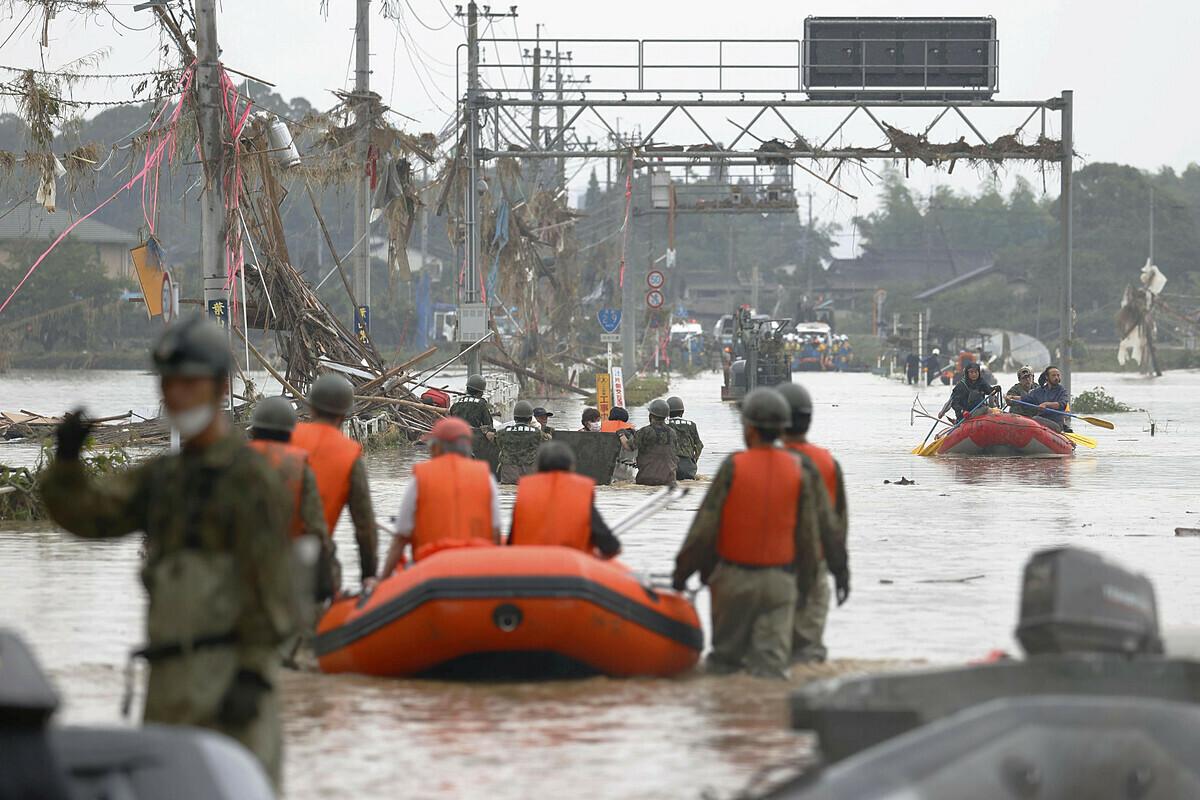 Người dân được lực lượng phòng vệ Nhật Bản đưa khỏi khu vực bị ngập lụt ở làng Kuma. Ảnh: Kyodo News.