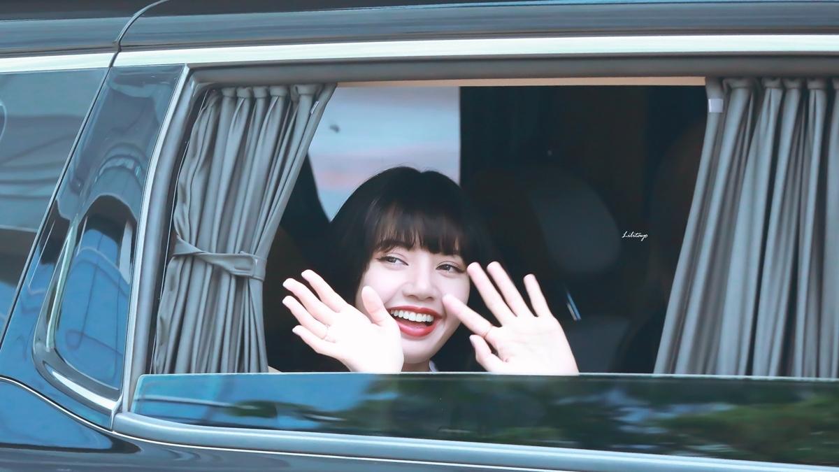 Lisa vẫy tay chào fan trên đường đi làm về.