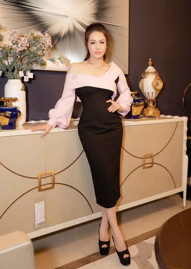 Nhật Kim Anh chọn thiết kế bất đối xứng. Cô cột tóc cao, đeo phụ kiện đồng điệu.