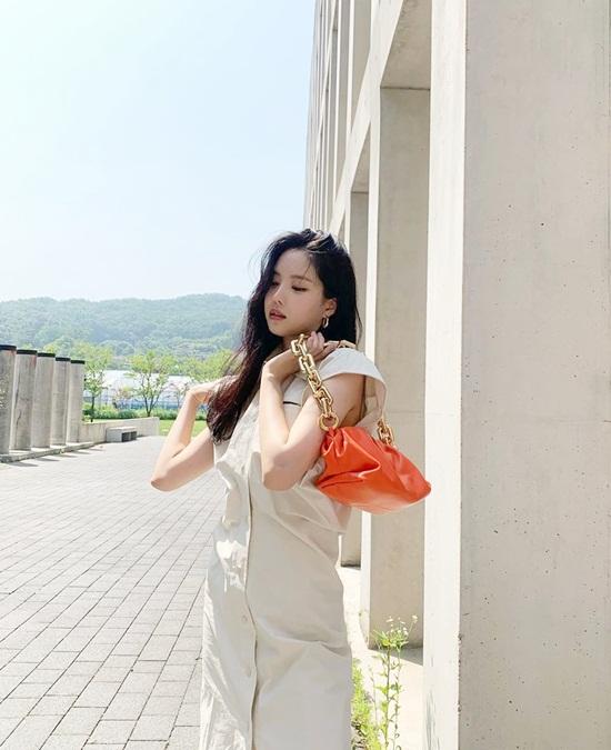 Na Eun xách túi tạo dáng sang chảnh.