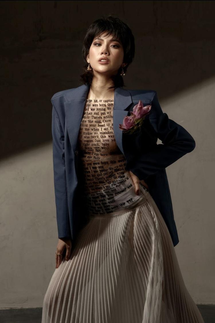 Quỳnh Hoa phối áo in chữ xuyên thấu mỏng tang, khoe ngực đầy cùng chân váy xếp ly trắng. Bên ngoài, cô khoác áo vest phom dáng rộng và dùng khuyên tai kim loại tạo điểm nhấn.