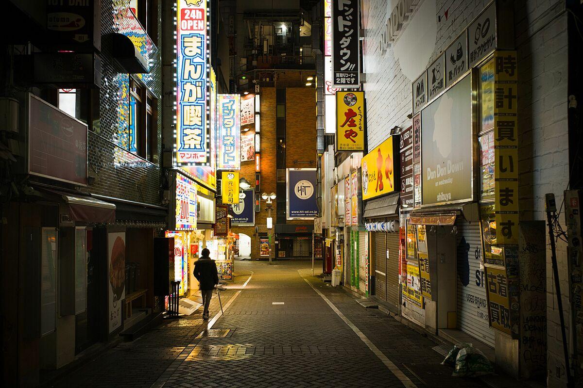 Một người đi bộ qua con hẻm vắng vào ban đêm ở quận Shibyua, Tokyo.