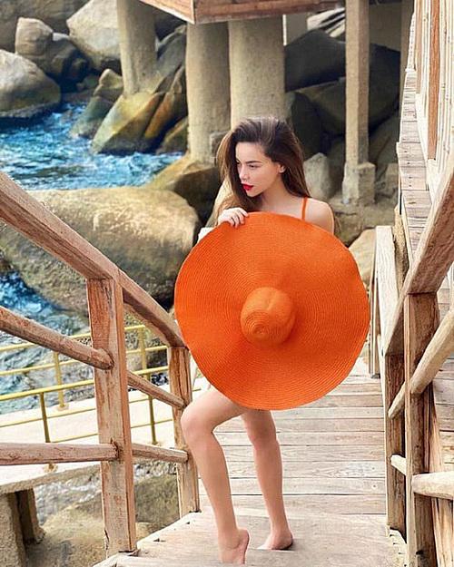 Nghỉ dưỡng tại một resort 5 sao ở Nha Trang cùng Kim Lý, Hà Hồ mặc bikini đi bơi, ngắm hoàng hôn trên biển. Cô thoải mái tạo dáng và khéo léo dùng mũ rộng vành, che vòng hai lớn.