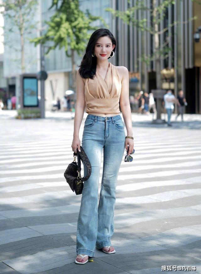 Thịnh hành nhất phải kể đến các mẫu quần jeans ống loe nhẹ, giúp ăn gian vóc dáng cực hiệu quả. Cô gái này kết hợp bộ cánh sang chảnh cùng sandals kiểu xỏ ngón - cũng là một xu hướng đang đắt khách.