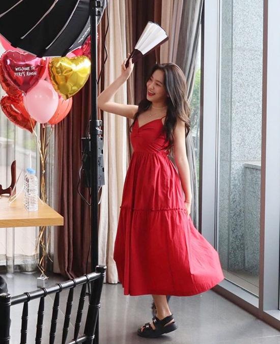 Yeri cầm quạt nhảy múa vui vẻ trong chiếc đầm hai dây màu đỏ.
