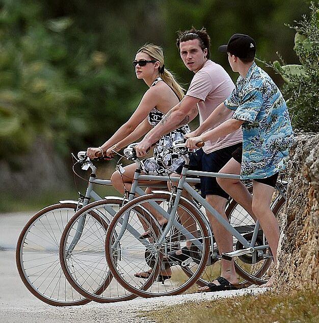 Nicola diện váy lụa Chanel đi đạp xe, bên cạnh là Brooklyn và Cruz.  Ảnh: Cobra Team/Backgrid