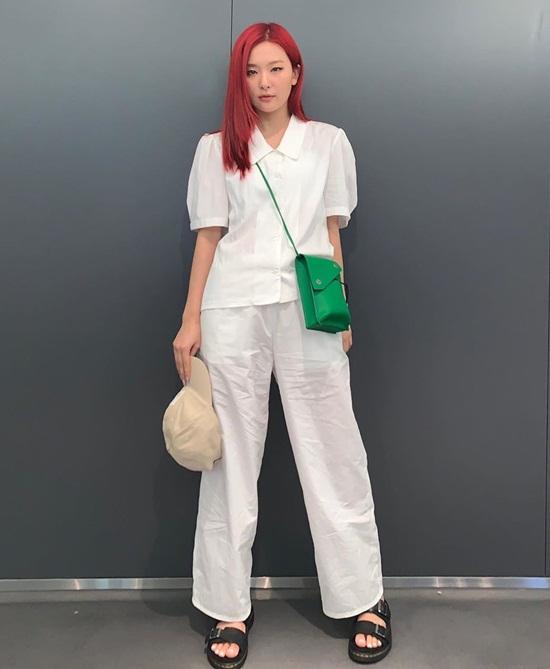 Seul Gi mặc set đồ trắng thoải mái, tô điểm bằng chiếc túi nhỏ màu xanh lá.