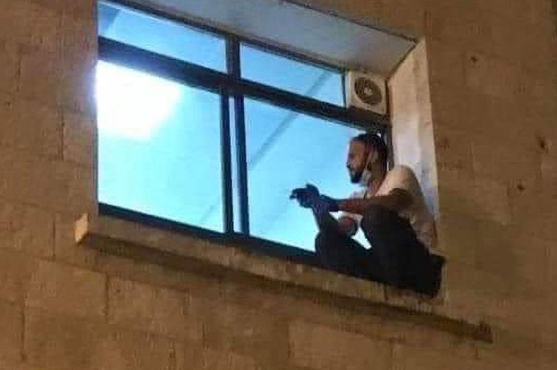 Chàng trai trèo lên gờ cửa sổ bên ngoài bệnh viện để nhìn mẹ trong phòng điều trị tích cực.
