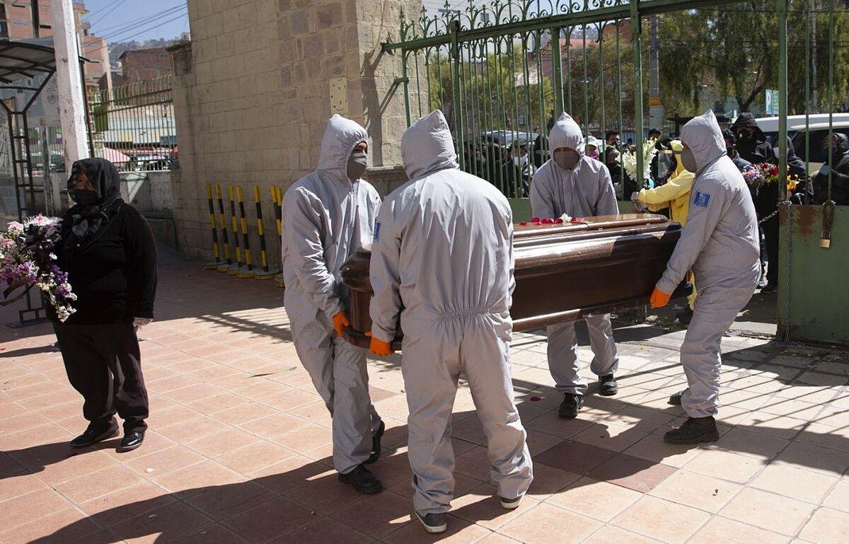 Nhân viên nhà tang lễ mặc đồ bảo hộ khiêng quan tài của một người đàn ông vào Nghĩa trang ở La Paz, Bolivia ngày 21/7. Ảnh: AP.