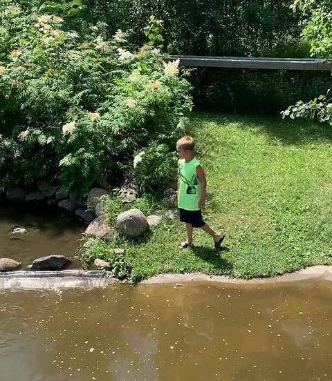 Bé trai đứng ngay gần mép hồ.