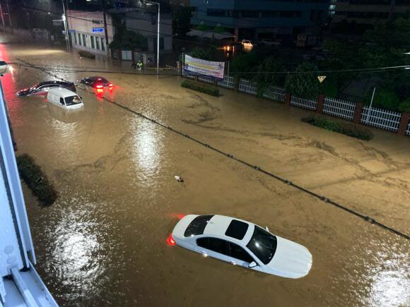 Những phương tiện bị mắc kẹt giữa dòng nước dâng cao vì mưa lớn.