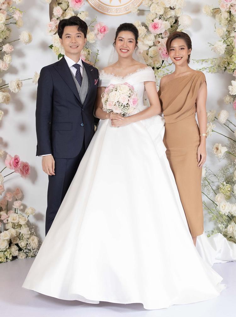 Khả Ngân mặc đầm lệch vai gam màu nâu pastel, chụp hình cùng cô dâu chú rể.