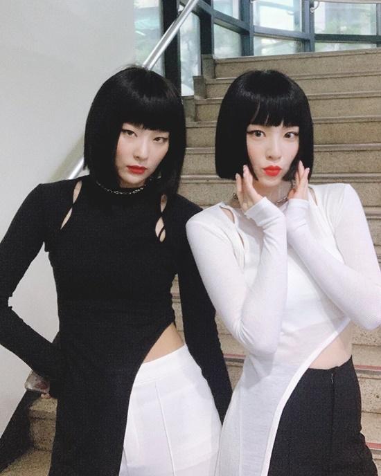 Irene (phải) và Seul Gi như song sinh khi đội tóc giả giống hệt, diện đồ đen - trắng đồng điệu.