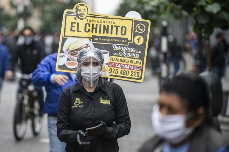 Một người phụ nữ quảng cáo cho nhà hàng bánh sandwich ở trung tâm thành phố Lima - nơi cách ly bắt buộc do đại dịch.