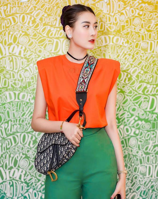 Áo thun độn vai là kiểu trang phục đơn giản nhưng đặc biệt có sức hút trong mùa hè năm nay. Hàng loạt người đẹp Việt đua nhau diện kiểu áo mang hơi hướng chiến binh, tạo hình ảnh mạnh mẽ, sang trọng. Hà Lade dự sự kiện thời trang với set đồ color block, trong đó điểm nhấn là thiết kế độn vai màu cam nổi bật.