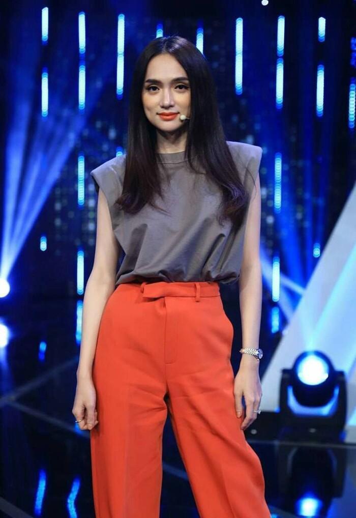 Hương Giang cũng kết hợp sơ mi độn vai và quần ống suông, tuy nhiên cô chọn tông màu trung tính hơn.