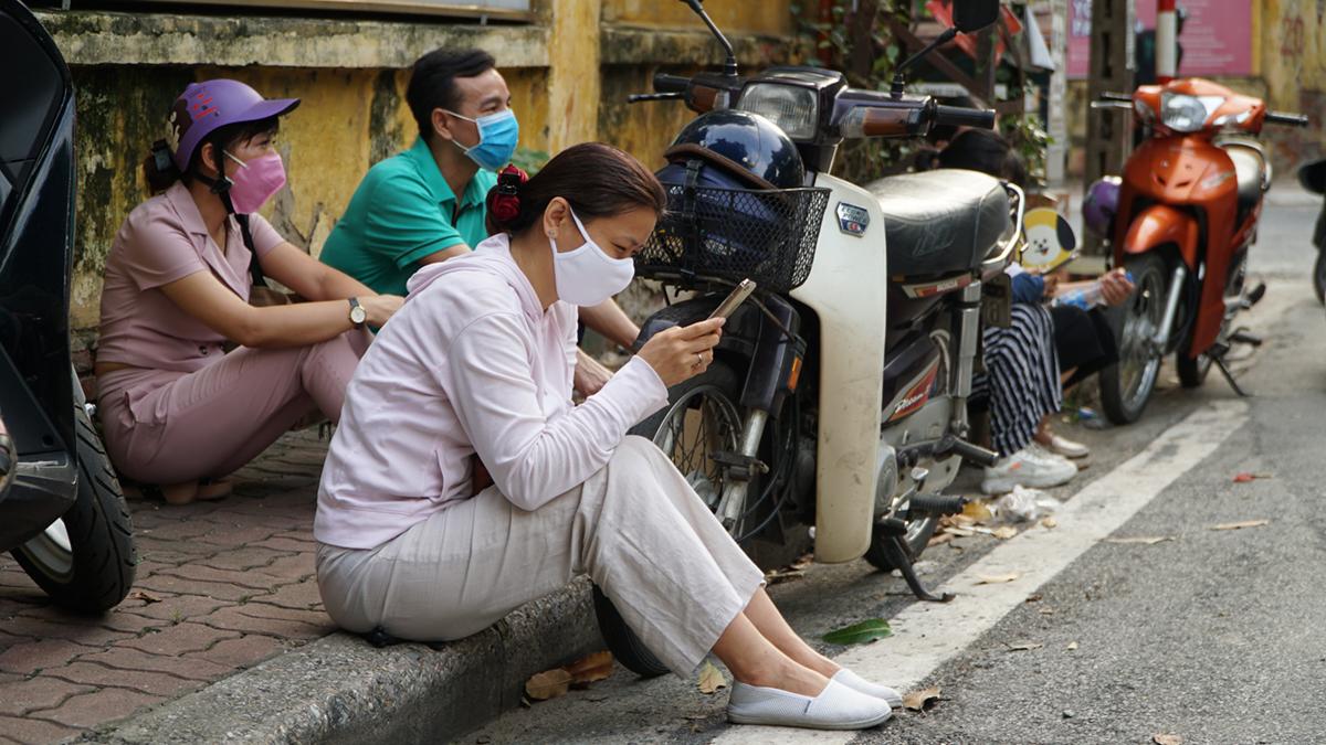 Chị Hương ngồi chờ con trước điểm thi THPT Chu Văn An.