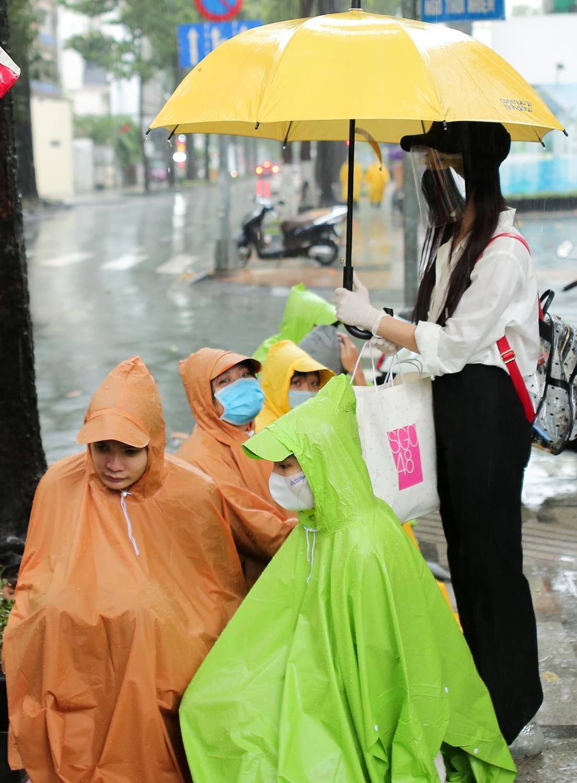 Thời tiết ở TP HCM chiều 9/8 và sáng 10/8 không mấy ủng hộ thí sinh khi có mưa lớn. Dù thế, các thành viên của nhóm không ngại đội mưa, đứng trước các cổng trường thi để tặng khẩu trang cho thí sinh.