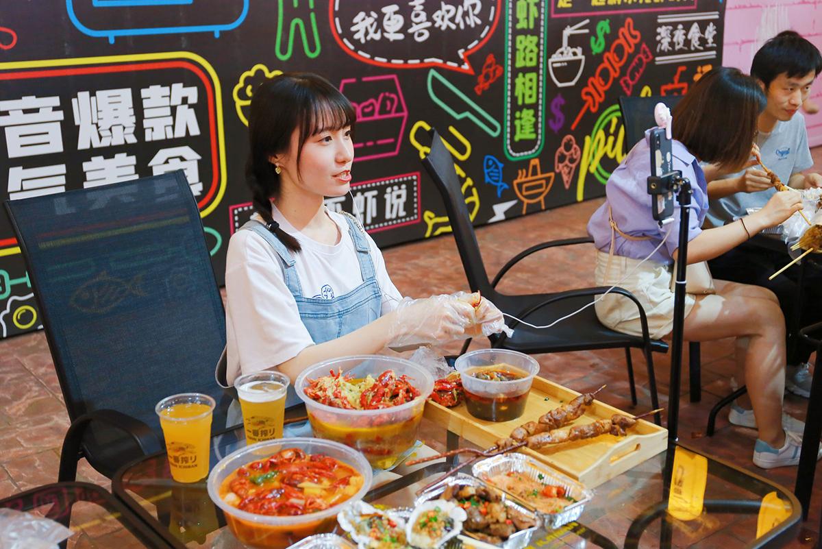 Food blogger live stream ăn uống trên điện thoại di động. Ảnh: Sipa.