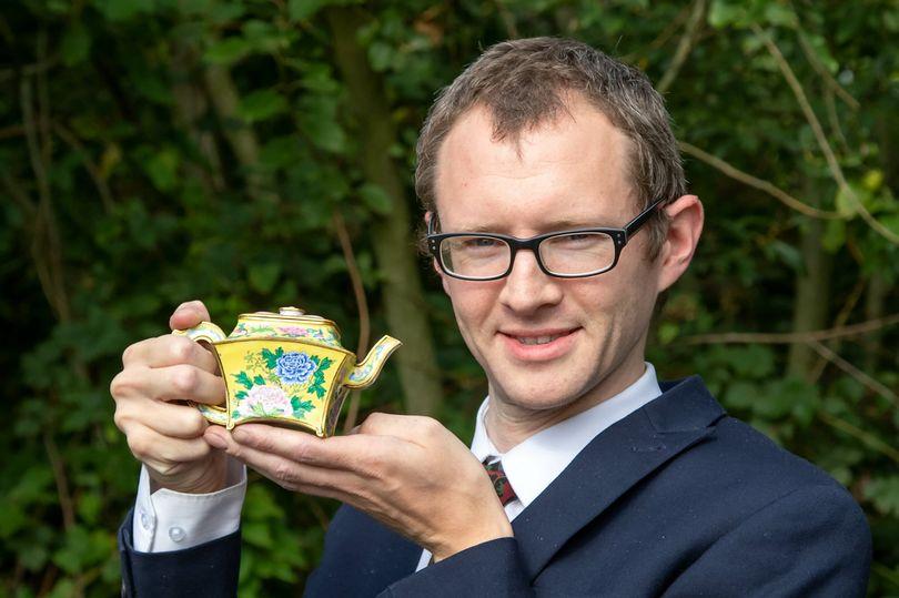 Nhà đấu giá Charles Hanson cầm chiếc ấm trà cổ.