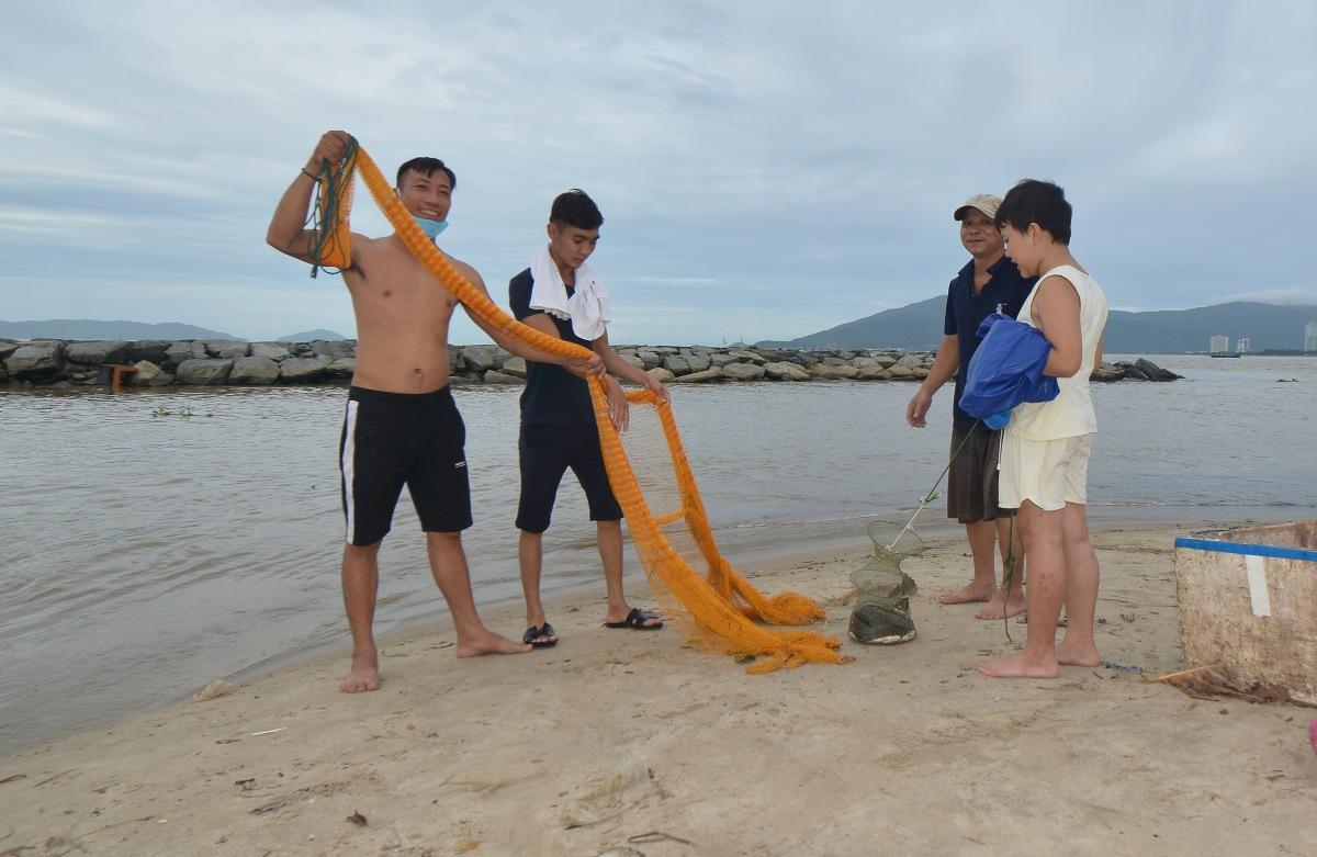 Dọc theo các cửa sông và cống nước thải đổ ra vịnh Đà Nẵng, sau khi nước rút, nhiều người dân địa phương tập trung đánh bắt cá.