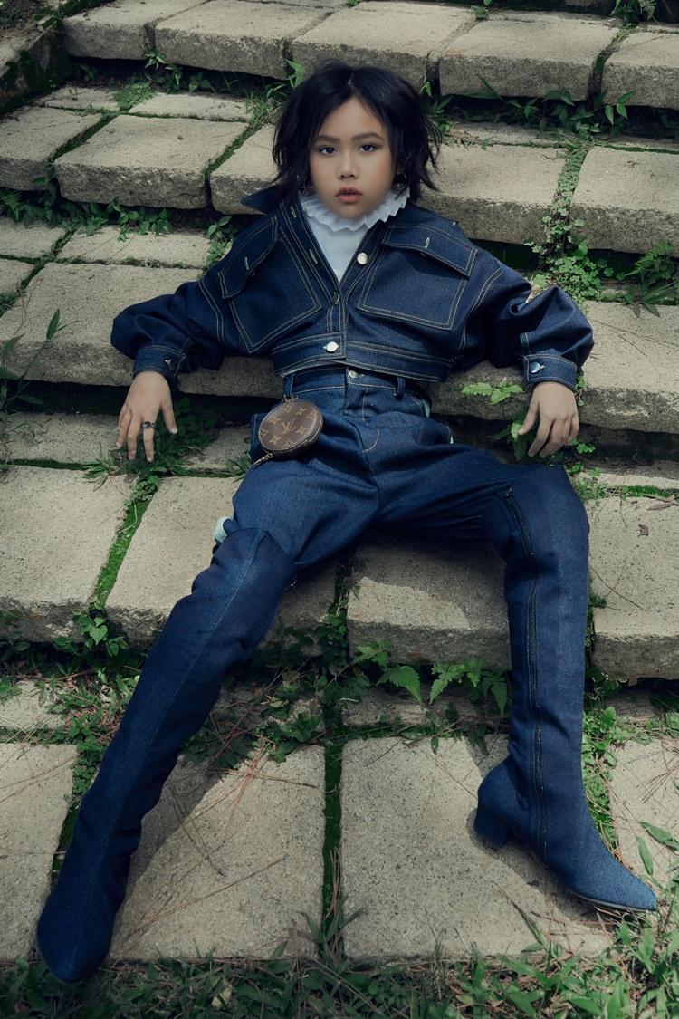Khánh An mặc set đồ làm từ chất liệu denim. Mẫu nhí 9 tuổi đeo phụ kiện Louis Vuitton.