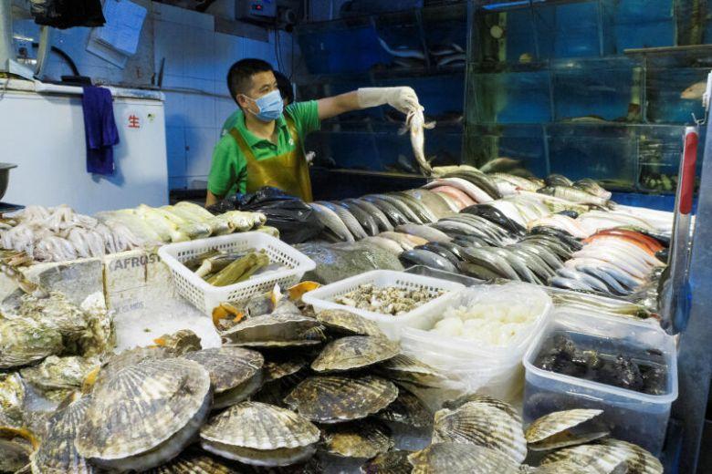 Một người buôn bán hải sản đông lạnh. Ảnh: Reuters.