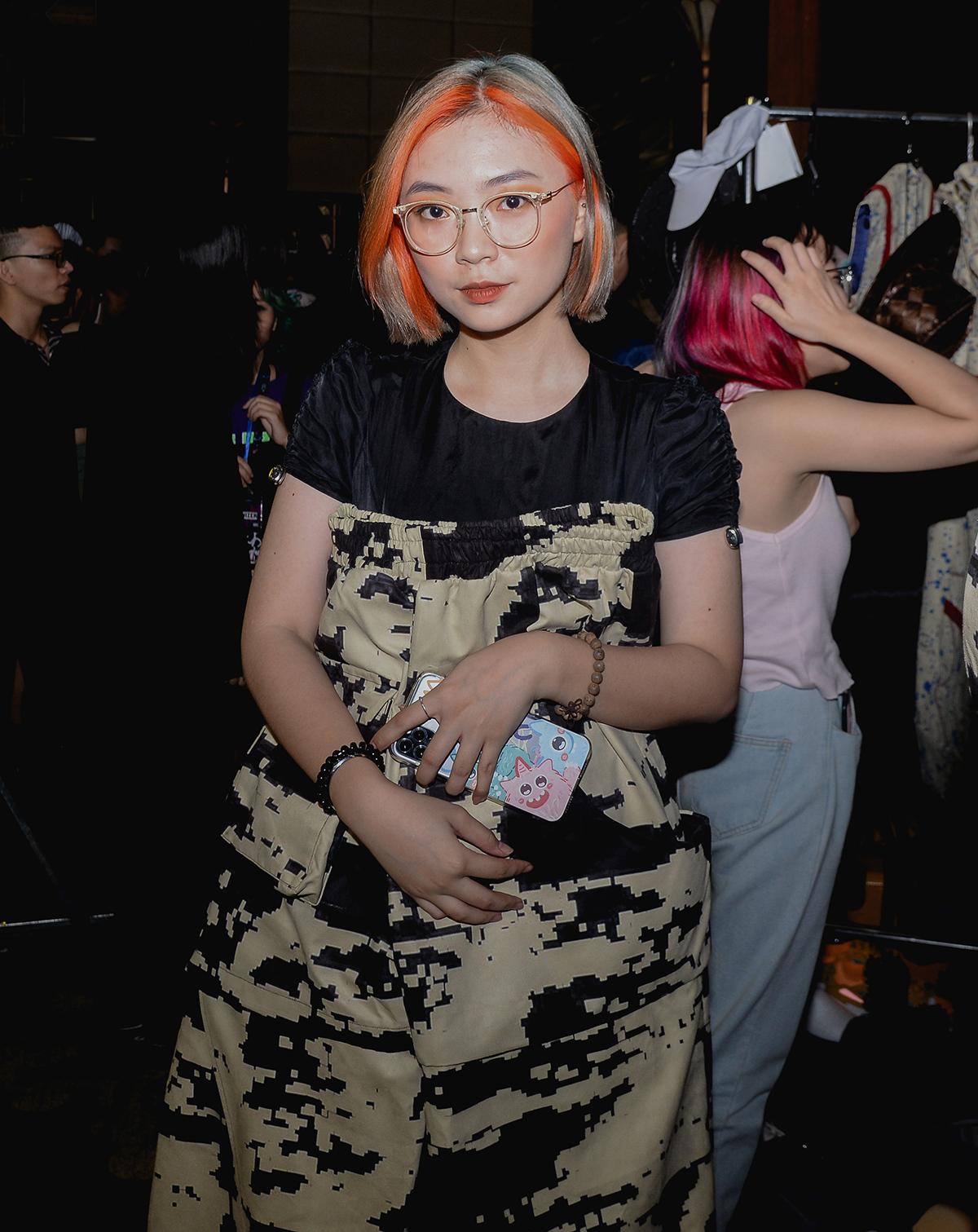 Chiếc váy bao tải giúp cô bạn này khoe cá tính ăn mặc riêng biệt. Mái tóc phẩy light cam và lối trang điểm tông xuyệt tông cũng cho thấy sự đầu tư trong diện mạo của nữ sinh viên.
