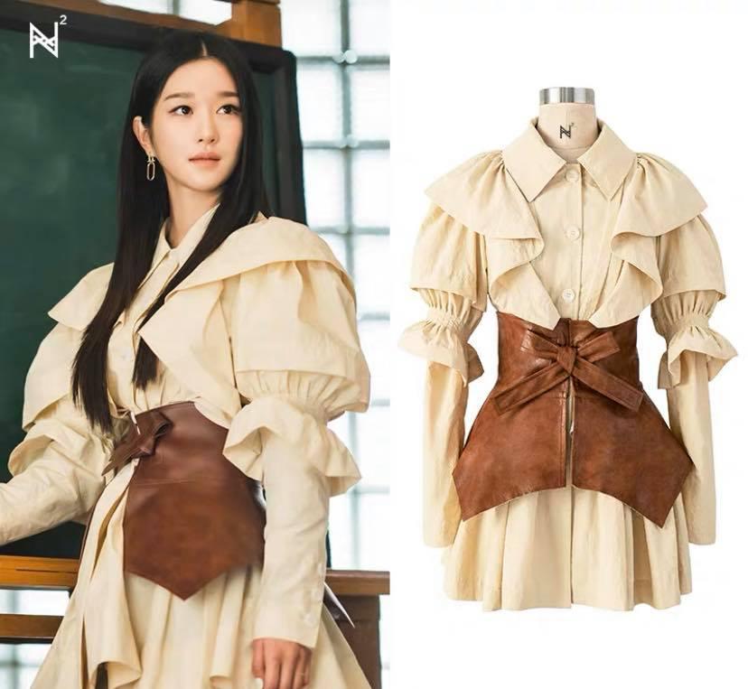 Một trong những thiết kế để lại ấn tượng sâu đậm nhất với khán giả mà Seo Ye Ji từng diện là bộ váy sơ mi với thiết kế vai phồng, tay diềm bèo rất kiểu cách. Đi kèm chiếc váy dáng xòe là thắt lưng da kiểu obi, giúp tạo vẻ cổ điển nhưng vẫn cá tính. Trong phim, Seo Ye Ji diện váy của NTK Kim Min Ju, đi kèm thắt lưng Loewe. Hiểu được tâm lý muốn mặc như thần tượng nhưng không phải ai cũng có hàng chục triệu đồng để mua hàng chính hãng, nhiều shop thời trang sản xuất đồ ăn theo và rất đắt khách.
