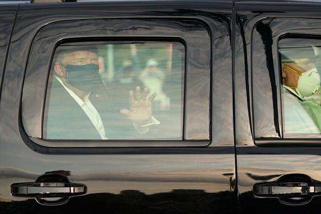 Tổng thống Trump ngồi trong xe vẫy tay chào người ủng hộ bên ngoài Walter Reed ngày 4/10. Ảnh: AFP.