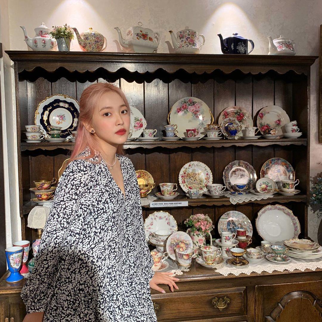 Yeri (Red Velvet) cũng không quá đặt nặng việc mix đồ trong các buổi trà bánh. Nữ idol diện váy hoa dáng suông đơn giản thích hợp để dạo phố, cách làm tóc, trang điểm cũng rất nhẹ nhàng.