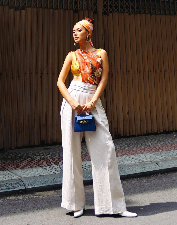 Khánh Linh sáng tạo khi biến khăn Hermes thành áo và turban. Trên tay, nàng fashionista cũng xách chiếc túi đẳng cấp cùng thương hiệu.