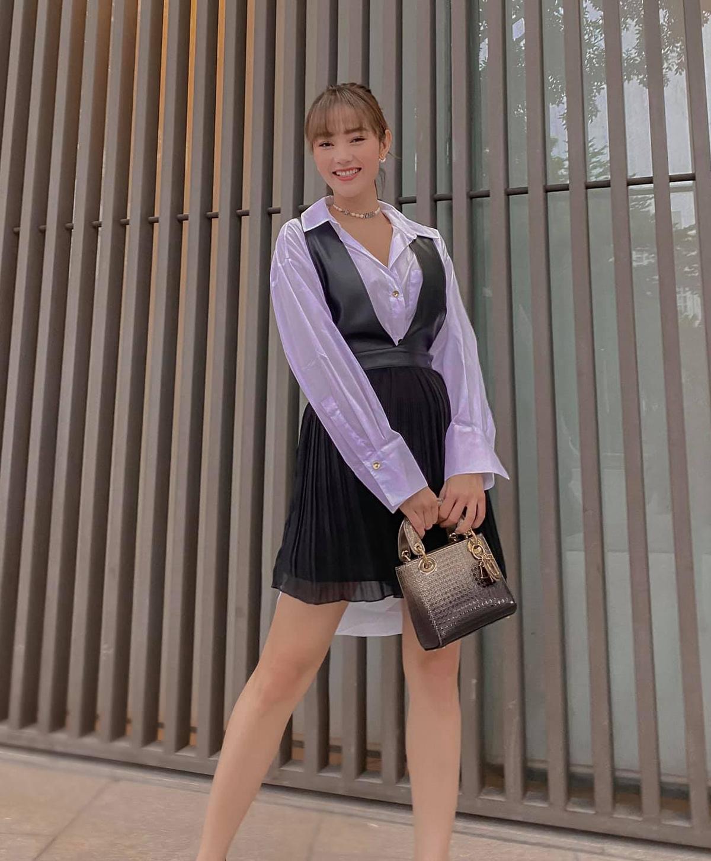 Diện sơ mi trắng và váy yếm, Minh Hằng trông trẻ trung như nữ sinh. Chiếc túi Lady Dior màu ombre hoàn thiện diện mạo sang chảnh cho nữ ca sĩ.