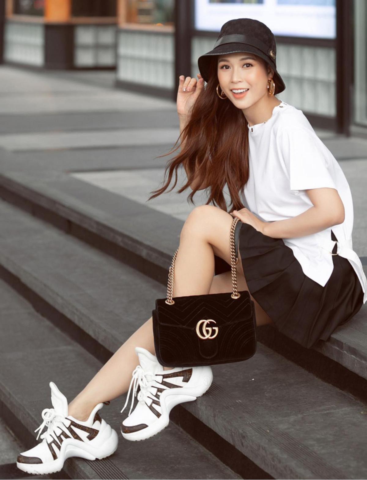 Chỉ diện hai tông đen - trắng cơ bản, Sam vẫn nổi bật nhờ cách mix đồ trẻ trung. Áo phông, chân váy xòe được cô mix cùng mũ và túi Gucci, đi kèm là sneakers Louis Vuitton hầm hố.