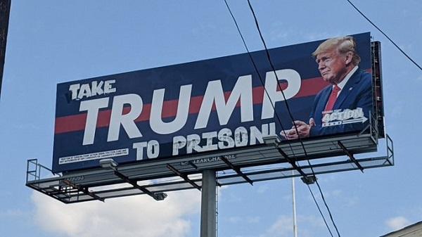 Biển quảng cáo ban đầu chỉ có chữ TRUMP, nay đã bị sửa đổi thành Hãy tống TRUMP vào tù.