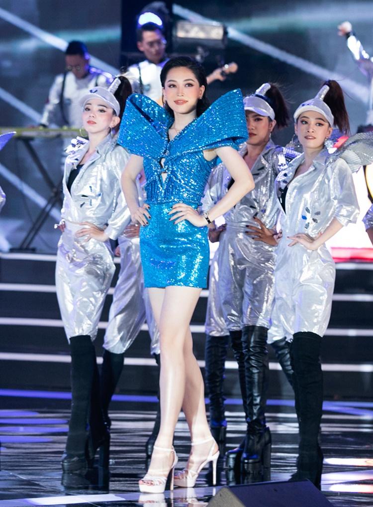 Á hậu Phương Nga khoẻ khoắn,cá tính trong chiếc váy sequins xanh dựng vai mạnh mẽ. Những đường dập ly vải đan xen khéo léo cùng điểm cột dây đẹp mắt tôn lên nét tươi trẻ của nàng á hậu.