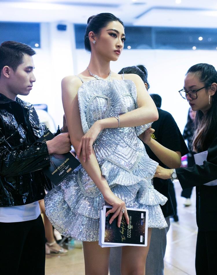 Lương Thùy Linh được nhà thiết kế Trần Ninh Hưng (trái) sửa sang trang phục trước khi lên sân khấu. Cô mặc thiết kế ánh bạc, đảm nhận vai trò MC. Chiếc váy được tạo nên từ những đường cấu trúc bèo nhún trên nền chất liệu sequins kết hợp đính kết thủ công tỉ mỉ.