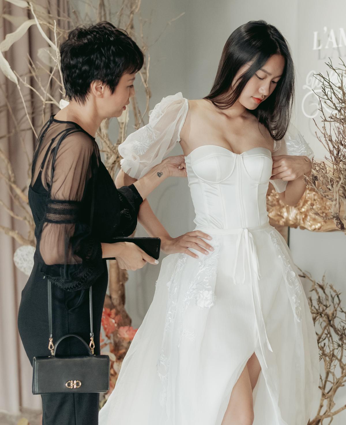 Người đẹp 19 tuổi được mẹ lựa chọn cho nhiều dáng váy cưới khác nhau. Cô khá ưng ý với mẫu đầm cúp ngực tay bồng, giúp cô tôn lên vóc dáng gợi cảm.