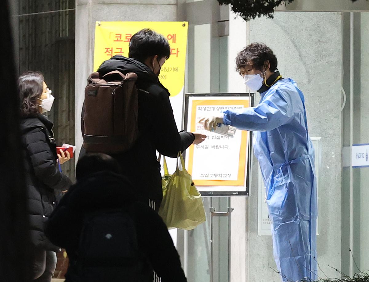 Cán bộ xịt nước rửa tay cho thí sinh tại trường trung học ở Seoul ngày 3/12. Ảnh: Yonhap.