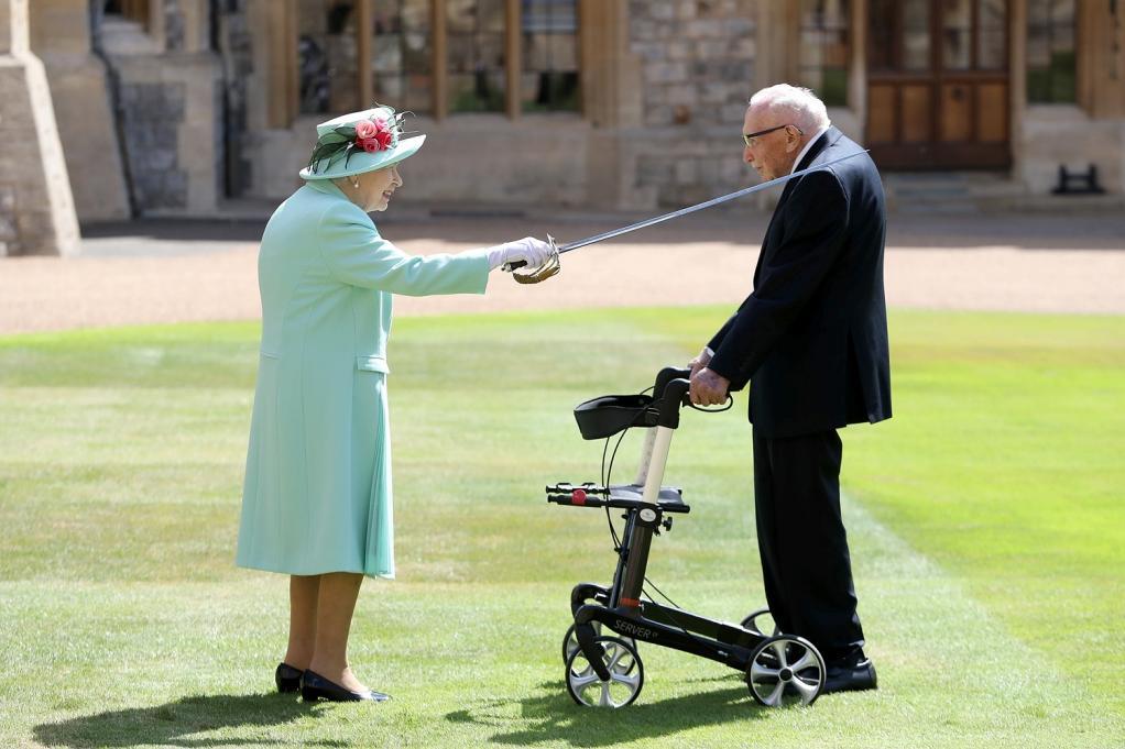 Nữ hoàng Elizabeth phong tước hiệp sĩ cho cựu binh 100 tuổi Tom Moore tại lâu đài Windsor sau khi ông gây quỹ 32 triệu bảng (40 triệu USD) cho cuộc chiến chống dịch Covid-19. Ảnh:Getty.