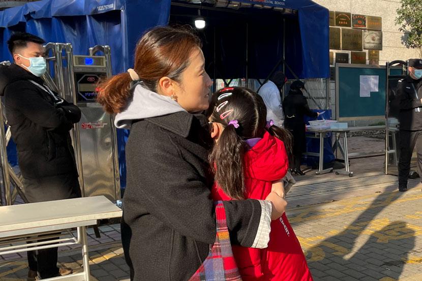 Người mẹ an ủi con gái trong khi chờ bố về nhà lấy thẻ căn cước để vào trung tâm thi tiếng Anh ở Thượng Hải, ngày 19/12.