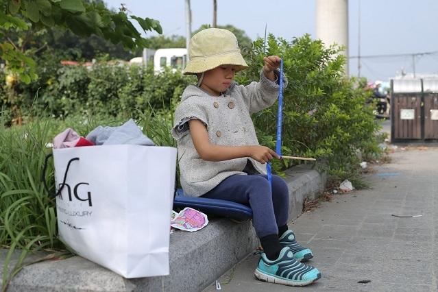 Hình ảnh Huyền Trang ngồi chờ bố trong công viên mỗi khi đi bán hàng.