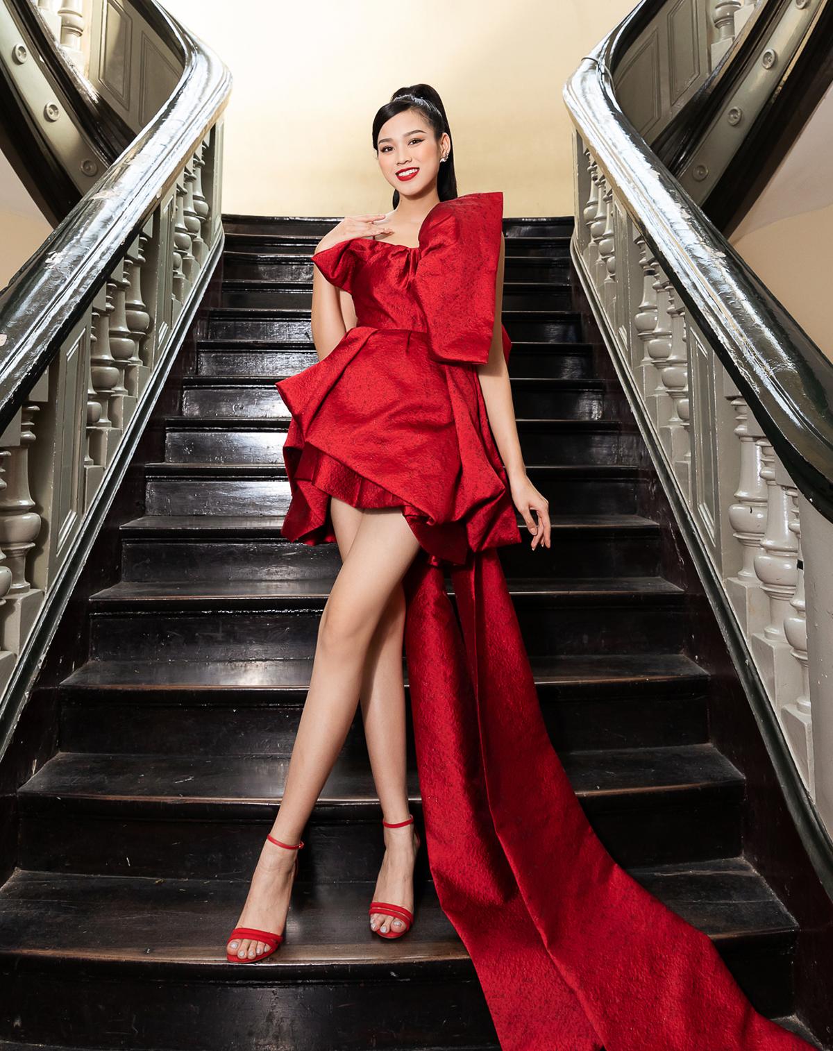 Hoa hậu Việt Nam 2020 Đỗ Thị Hà khoe đôi chân dài 1,11 m trứ danh cùng chiếc váy ngắn, phía sau có tà dài xếp nếp cầu kỳ.