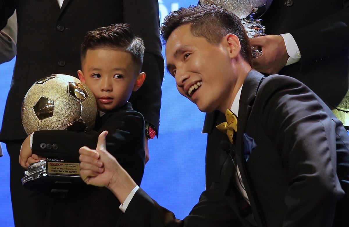 Cậu bé chia sẻ niềm vui cùng bố trong lần đầu nhận danh hiệu cao quý ở sự nghiệp bóng đá.