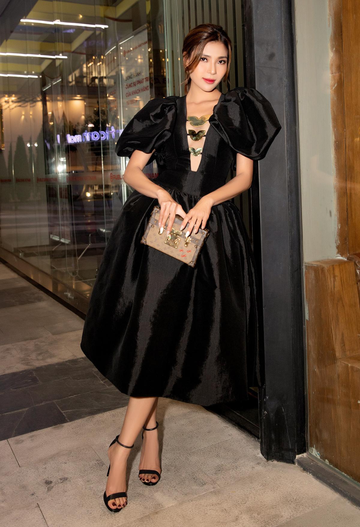 Người đẹp thu hút sự chú ý khi diện bộ váy đen tuyền với chi tiết khoét ngực, kết hình cánh bướm gợi cảm và tôn vòng một. Cô kết hợp túi Louis Vuitton tăng đẳng cấp.