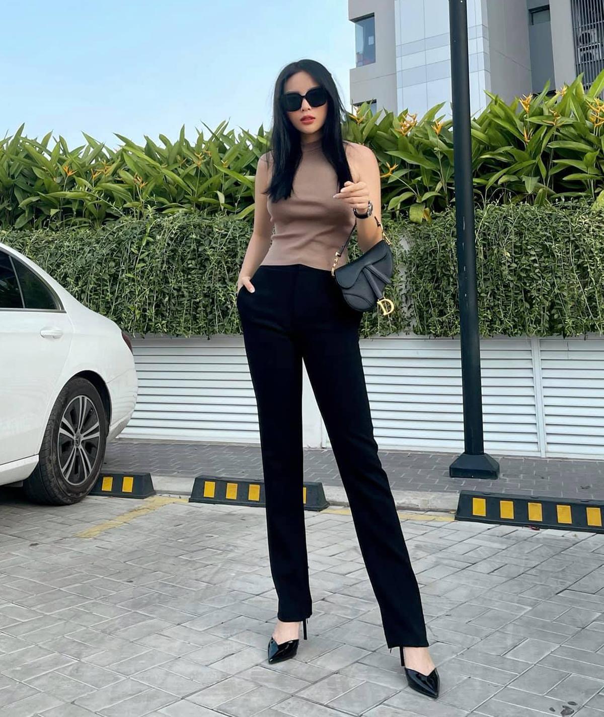 Kỳ Duyên có sẵn chân dài, dáng chuẩn nên không cần mix cầu kỳ vẫn nổi bật. Hoa hậu thần thái ngút ngàn trên phố chỉ với tanktop dệt kim và quần suông đen.
