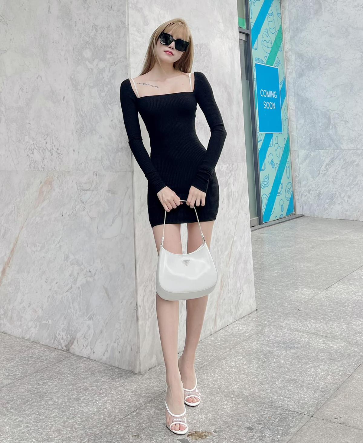 Diện chiếc váy đen ôm sát, Thiều Bảo Trâm khoe đường cong sexy cùng đôi chân nuột nà. Cách mix phụ kiện tông trắng giúp nữ ca sĩ hoàn thiện diện mạo chuẩn phong cách Y2K.